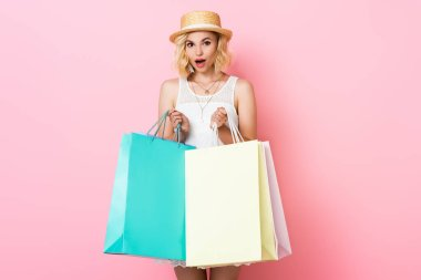 Surprised woman in straw hat and white dress holding shopping bags on pink stock vector