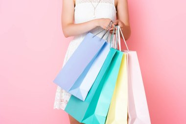 Cropped view of young woman holding shopping bags on pink stock vector