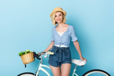 Woman in straw hat standing near bicycle and looking at camera on blue stock vector