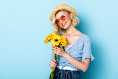 Woman in straw hat and sunglasses holding flowers on blue stock vector