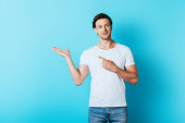 Man in white t-shirt pointing with hand and finger on blue background