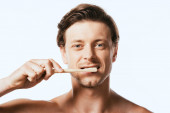 Shirtless man looking at camera while brushing teeth isolated on white