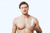 Muskulöser Mann hält Glas mit Zahnbürsten und Zahnpasta isoliert auf weiß