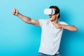 Fotografie Mladý muž v bílém tričku gestikulace při použití vr sluchátka na modrém pozadí