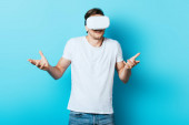 Man in white t-shirt and vr headset showing shrug gesture on blue background