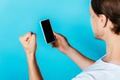 Muž ukazuje jo gesto a drží smartphone s prázdnou obrazovkou na modrém pozadí