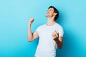 Mladý muž ukazuje ano gesto při držení smartphone na modrém pozadí
