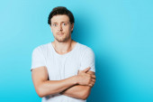 Worried man in white t-shirt with crossed arms looking at camera on blue background