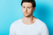 Serious man in white t-shirt looking at camera on blue background