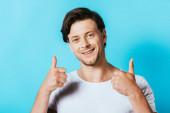 Mladý muž v bílém tričku ukazující palce nahoru na kameru na modrém pozadí