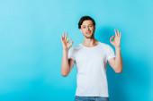 Fiatal férfi fehér pólóban mutatja rendben gesztus kamera kék háttér