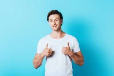 Young man in white t-shirt showing thumbs up on blue background stock vector