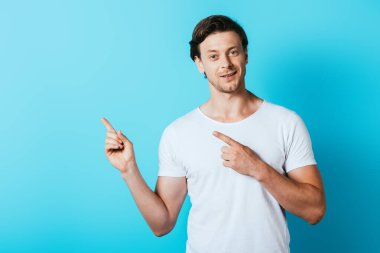 Man in white t-shirt pointing with fingers on blue background stock vector