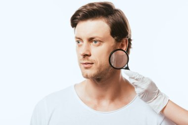 Young man looking away near dermatologist with magnifying glass isolated on white stock vector