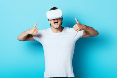 Young man in vr headset showing thumbs up on blue background stock vector