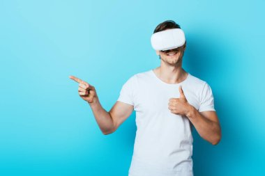Man in white t-shirt and vr headset showing thumb up and pointing with finger on blue background stock vector