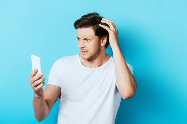 Thoughtful man with hand near head using smartphone on blue background stock vector