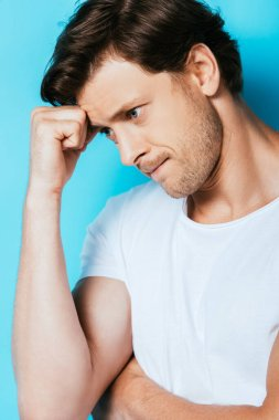 Pensive man in white t-shirt looking away on blue background stock vector