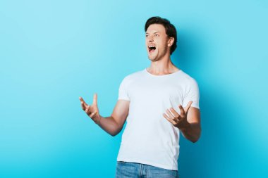 Angry man in white t-shirt screaming on blue background stock vector