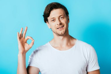 Man in white t-shirt showing okay gesture on blue background stock vector