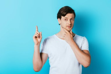 Young man in white t-shirt having idea on blue background stock vector