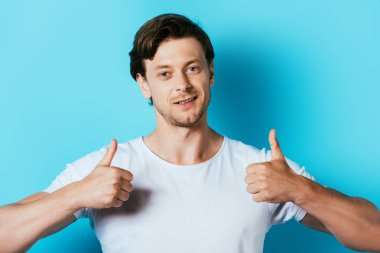 Man in white t-shirt showing thumbs up on blue background stock vector