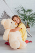 girl in white t-shirt hugging teddy bear while sitting on floor near play tent