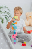 selective focus of boy in pajamas sitting on floor and playing with multicolored building blocks