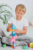 concentrated boy in pajamas sitting on floor and playing with colorful building blocks