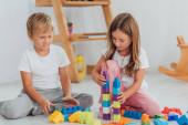 Konzentrierte Kinder im Pyjama, die auf dem Boden mit Bauklötzen spielen