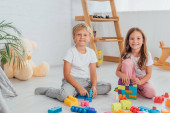 excited brother and sister in pajamas sitting on floor near building blocks and looking at camera