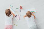vrchní pohled na bratra a sestru v pyžamu ležících na podlaze a kreslených plstěnými pery v náčrtcích