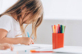 selective focus of girl in white t-shirt drawing with felt pen while sitting at table
