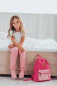 rozrušená dívka v pyžamu sedí na posteli v blízkosti školní batoh na podlaze