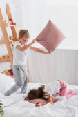 sister and brother having fun while fighting with pillows in bedroom