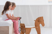 KYIV, UKRAINE - JULY 21, 2020: selective focus of brother and sister in pajamas playing video game near rocking horse
