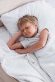 pohled shora chlapec spí na bílém lůžkoviny v dopoledních hodinách