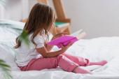 dívka v pyžamu sedí na posteli a čtení knihy ráno