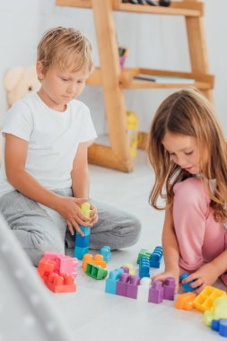 Selective focus of kids in pajamas sitting on floor and playing with building blocks stock vector