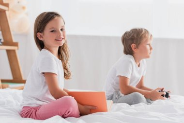 KYIV, UKRAINE - JULY 21, 2020: selective focus of girl with book looking at camera near brother playing video game in bedroom stock vector