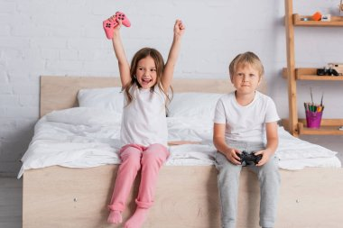 KYIV, UKRAINE - JULY 21, 2020: excited girl showing winner gesture near brother holding joystick in bedroom stock vector