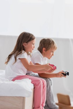 KYIV, UKRAINE - JULY 21, 2020: side view of focused children in pajamas playing video game stock vector