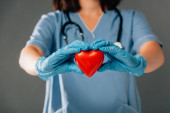 cropped view of doctor with stereoscope in latex gloves holding red heart isolated on grey