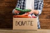 Photo cropped view of man putting clothes in cardboard box with donate lettering on wooden background, charity concept