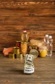 selektiver Fokus des Glases mit Geld und gespendeten Lebensmitteln auf hölzernem Hintergrund, Charity-Konzept