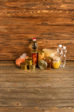 Groats near water, oil, canned food and honey on wooden background, charity concept stock vector