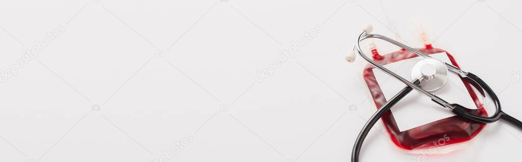 Blood donation package with blank label and stethoscope on white, panoramic shot stock vector