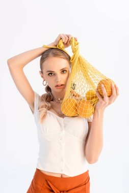 Fashionable woman posing with citrus fruits in string bag isolated on white stock vector