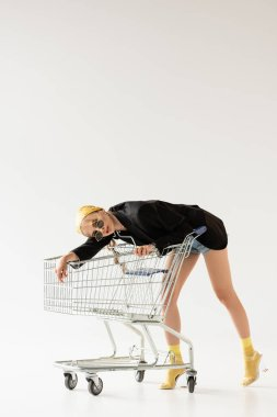 Fashionable woman in black and yellow outfit posing on shopping cart on white stock vector