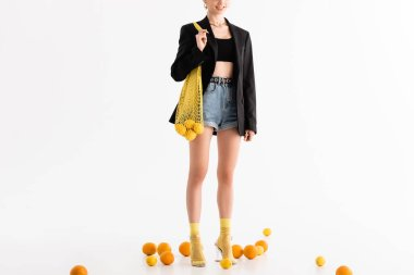 Cropped view of fashionable woman posing with string bag near scattered citrus fruits on white background stock vector